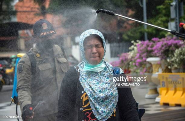 Public order agency officer sprays disinfectant over a woman before she enters a local government office as a precautionary move against the spread...