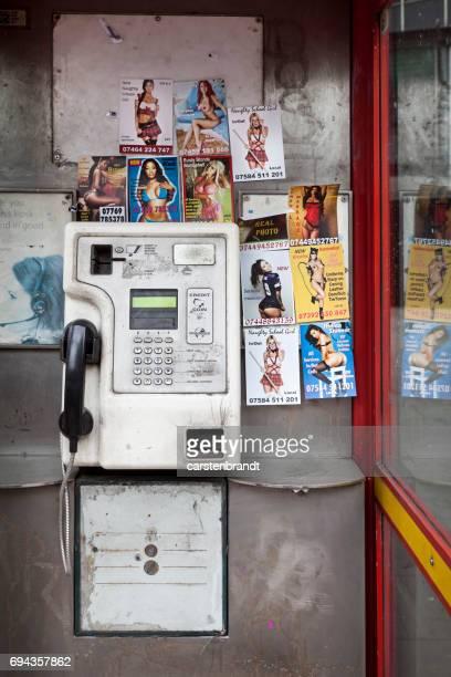 Öffentliches Telefon mit Prostituierten Flyer in London