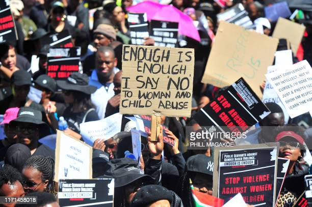 Public sector workers shout slogans as they hold banners during a protest march to The Union Buildings in Pretoria on September 27 as they commit...