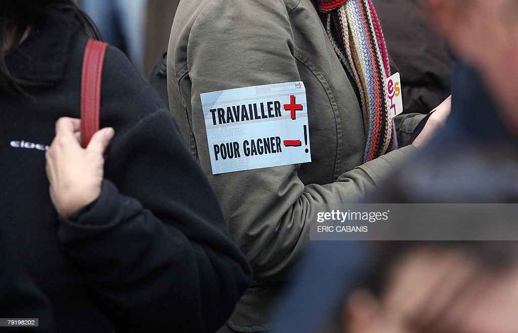 Public service employees demonstrate, 24 January 2008 in Toulouse, to protest against jobs cuts and low wages. Seven of the eight unions representing France's 5.2 million state employees called for the one-day strike and protest marches in Paris and other cities. A sticker reads 'to work more to earn less'.