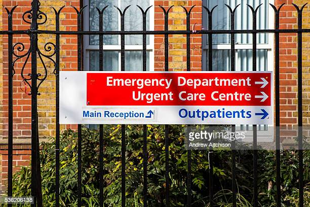 Public sign on metal fence directing people to the Emergency Department, Urgent Care Centre, Outpatients and Main Reception of University Hospital...