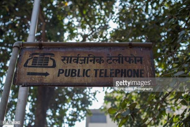 public telephone sign in mumbai - highlywood stock pictures, royalty-free photos & images