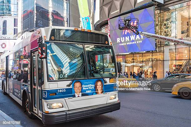 Public Transportation Bus in New York City Bluewhite bus driving in a prominent street in New York City A lot of traffic and advertisements in the...