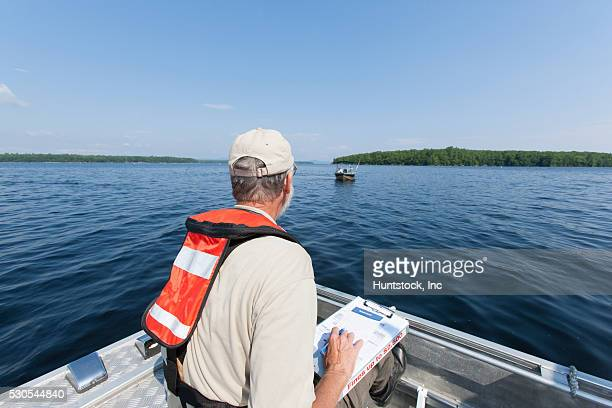 Public works engineer on service boat preparing to take public water samples from reservoir