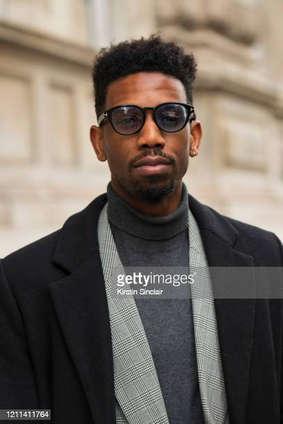 Publicist Joe Hagan wears a Versace suit Asos coat Tom Ford sunglasses during London Fashion Week February 2020 on February 18 2020 in London England