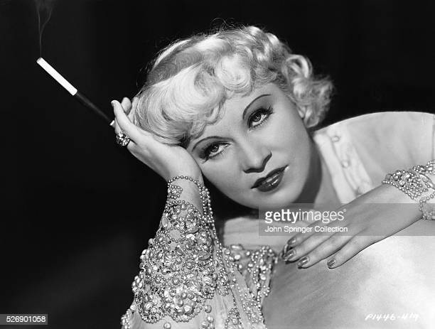 Publicity handout for Paramount Pictures of actress Mae West , in a head and shoulders photograph holding a cigarette. Ca. 1935.