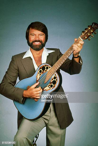 Publicity handout of bearded Country/Western musician Glen Campbell posing with a guitar