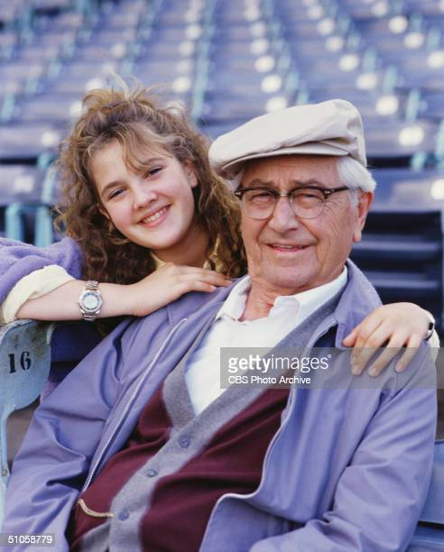 Publicity photo for the CBS television movie 'Conspiracy of Love' shows American actors Drew Barrymore and Robert Young sitting in a stadium 1987