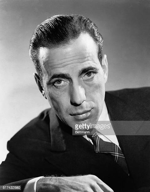 A publicity portrait of actor Humphrey Bogart leaning forward and wearing a suit and tie in a studio setting Ca 19301957