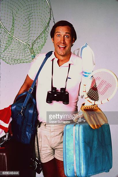 Publicity portrait of American actor and comedian Chevy Chase as he poses with suitcases for the film 'National Lampoon's Vacation' 1983