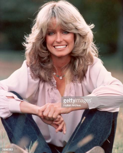 Publicity portrait of American actor and model Farrah Fawcett smiling while sitting outdoors in blue jeans and a mauve blouse