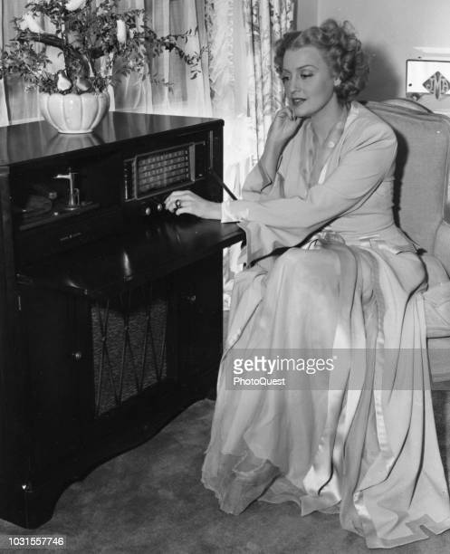 Publicity portrait of American singer and actress Jeanette MacDonald as she adjusts the dials of a General Electric Model 417 combination radio...