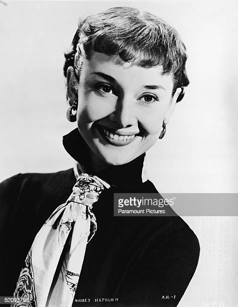 Publicity portrait of Belgian-born American actress Audrey Hepburn wearing a black shirt and print pattern cravat, 1953.