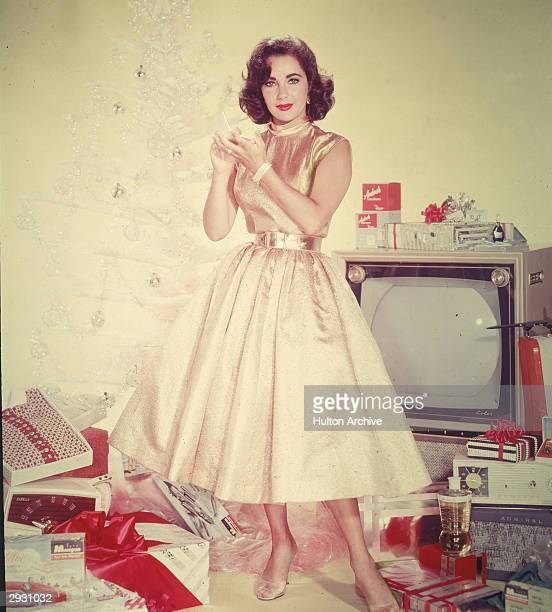 Publicity portrait of Britishborn actor Elizabeth Taylor in a yellow dress as she stands in front of an artificial Christmas tree amidst a pile of...