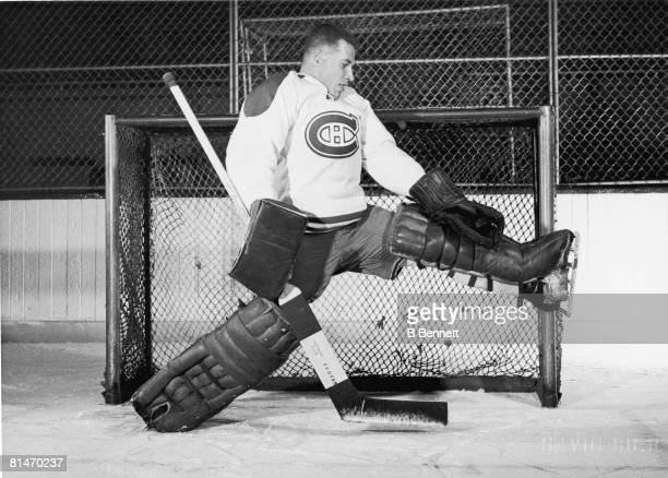 Publicity portrait of Canadian ice hockey player Gerry McNeil goalkeeper for the Montreal Canadiens as he stretches out a leg to make a save late...