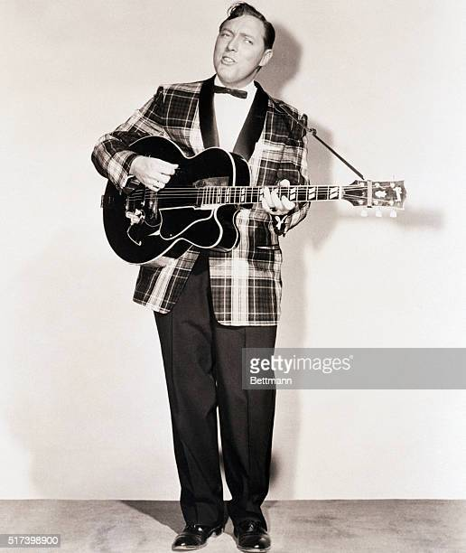 Publicity portrait of Decca recording artist Bill Haley He is shown fulllength playing guitar and singing