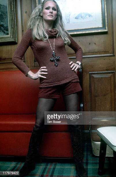 Publicity portrait of Swiss actress Ursula Andress as she poses in a turtleneck sweater, miniskirt, and knee-high boots, 1970s.