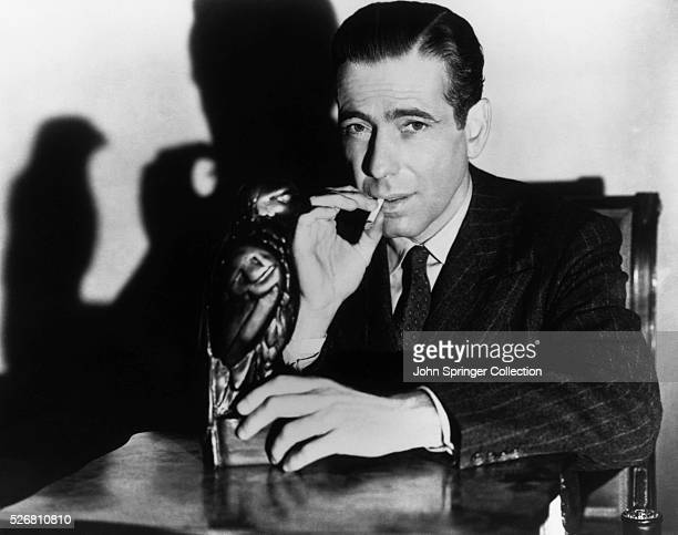 A publicity still from John Huston's The Maltese Falcon shows Humphey Bogart as Sam Spade sitting with the object of the title Motion pictured...