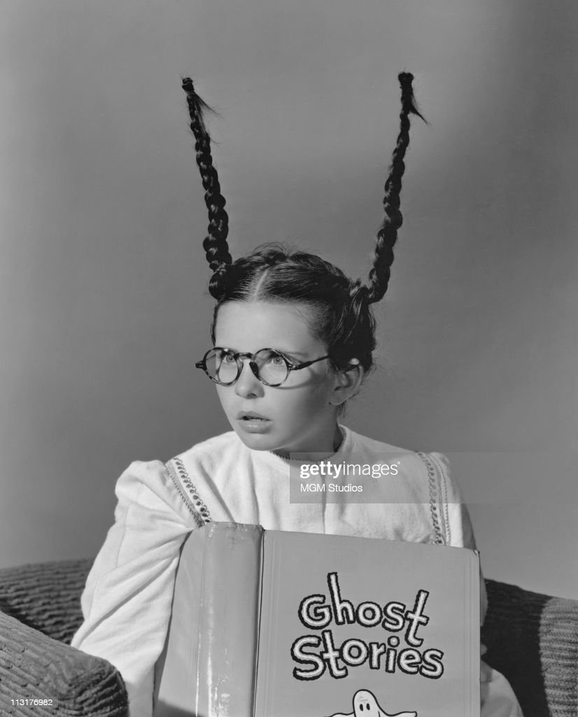 A publicity still of young actress Margaret O'Brien, with her pigtails up in the air and reading a ghost book, who will soon be starring in the MGM films 'The Unfinished Dance' and 'The Big City' in 1947.