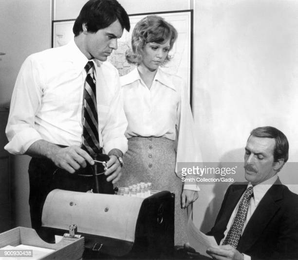 Publicity still showing three actors Robert Urich Maureen Reagan and Jack Hogan posing on set in an office/lab with a bag full of test tubes during...