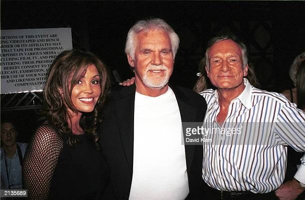 Publisher Hugh Hefner Singer Kenny Rogers and his wife Wanda pose at the Benchwarmer Trading Cards party at White Lotus in Hollywood July 2nd 2003