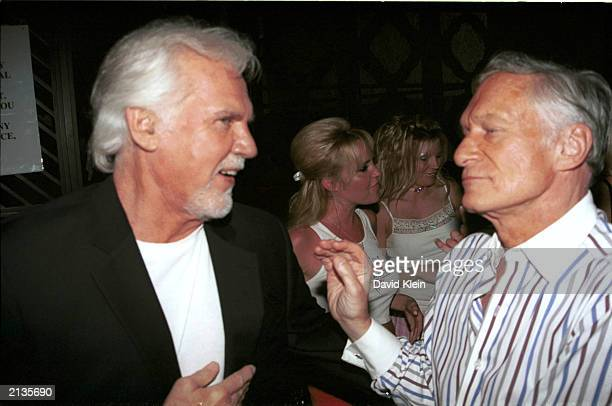 Publisher Hugh Hefner Singer Kenny Rogers talk at the Benchwarmer Trading Cards party at White Lotus in Hollywood July 2nd 2003