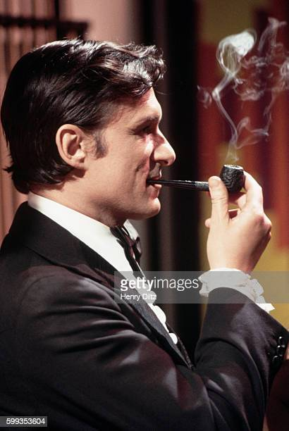 Publisher Hugh Hefner smokes his pipe on the sound stage during the filming of his television show Keyhole Hefner played the role of playboy and...