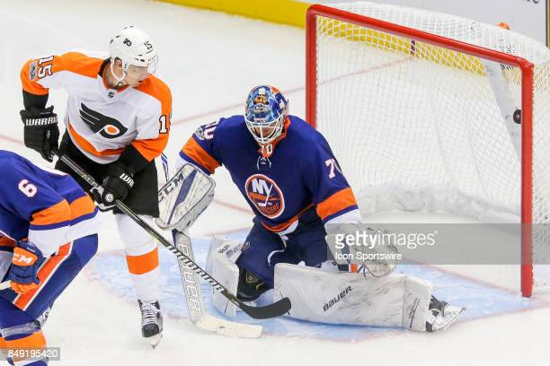 Puck enters net for goal past New York Islanders goalie Kristers Gudlevskis and Philadelphia Flyers center Jori Lehtera during the NHL preseason game...