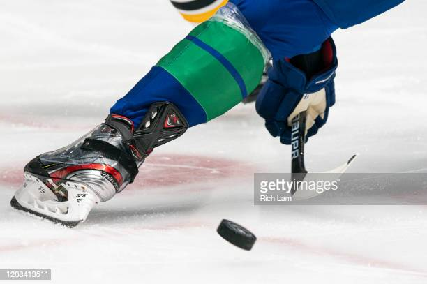 Puck flies out of a face-off circle during NHL action between the Vancouver Canucks and the Boston Bruins at Rogers Arena on February 22, 2020 in...