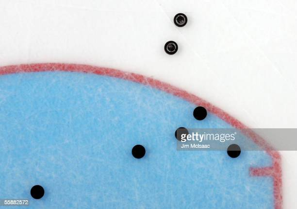 Pucks are seen on the ice in warmups prior to the start of the game between the New York Islanders and the Carolina Hurricanes on October 8, 2005 at...