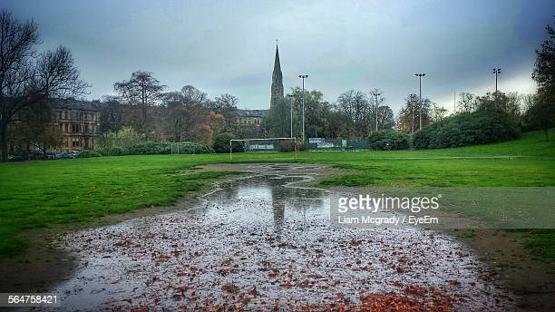 puddle in soccer field against cloudy sky - football pitch stock pictures, royalty-free photos & images