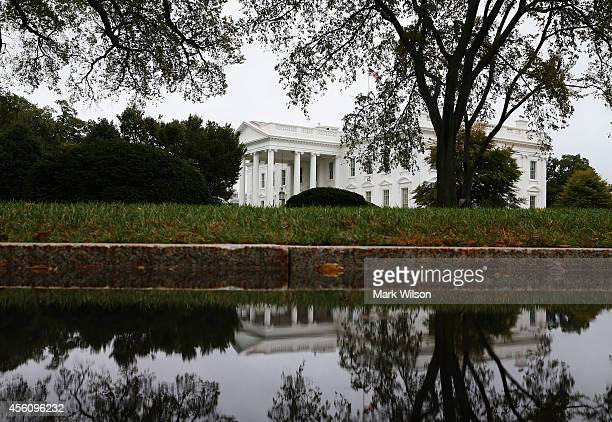 A puddle in the driveway reflects the White House and north lawn on September 25 2014 in Washington DC The Secret Service is investigating a recent...