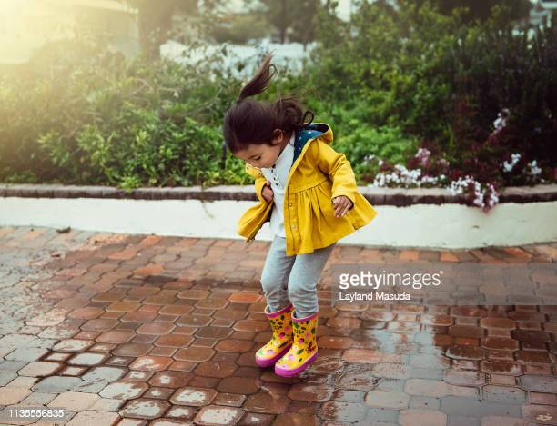 puddle jumping toddler girl - puddle stock pictures, royalty-free photos & images