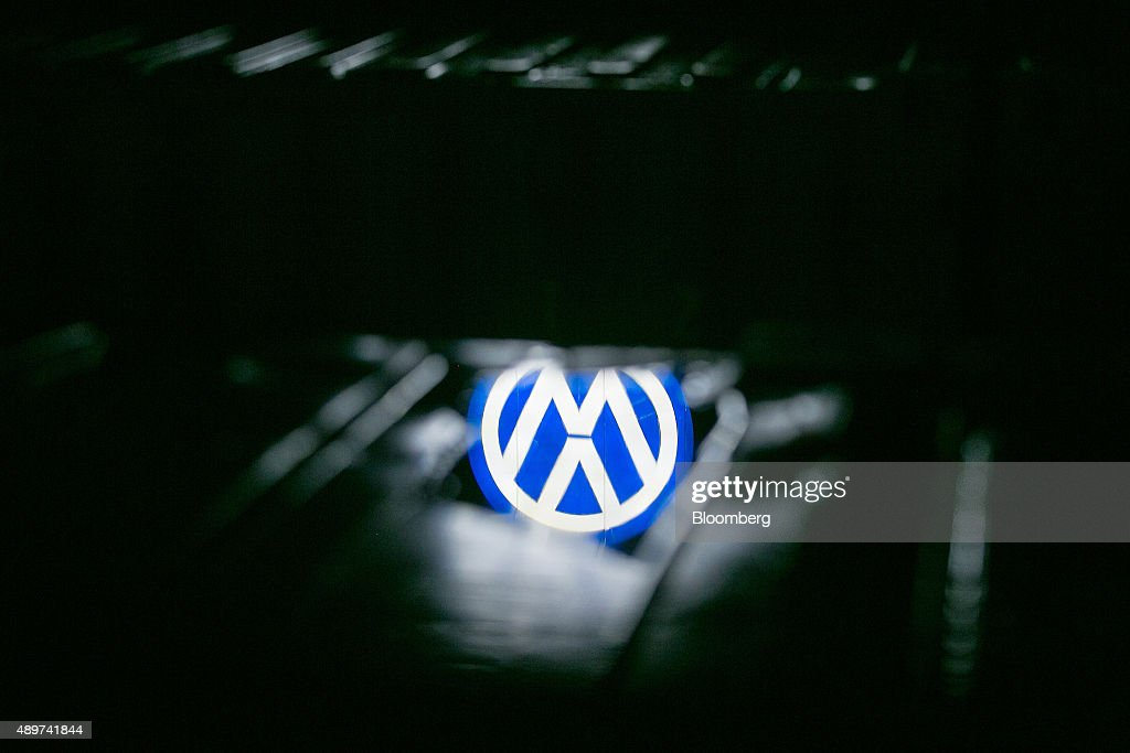 A puddle reflects the VW logo at night outside the Volkswagen AG headquarters in Wolfsburg, Germany, on Wednesday, Sept. 23, 2015. Volkswagen's escalating scandal over emissions-test cheating is beginning to ripple across the $10 trillion global corporate bond market. Photographer: Krisztian Bocsi/Bloomberg via Getty Images