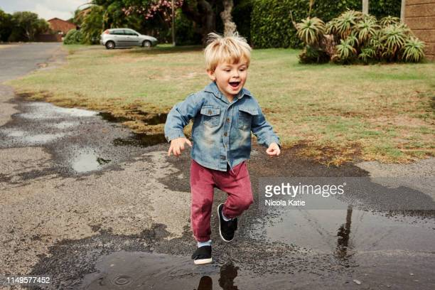 puddle splash frenzy! - waterhole stock pictures, royalty-free photos & images