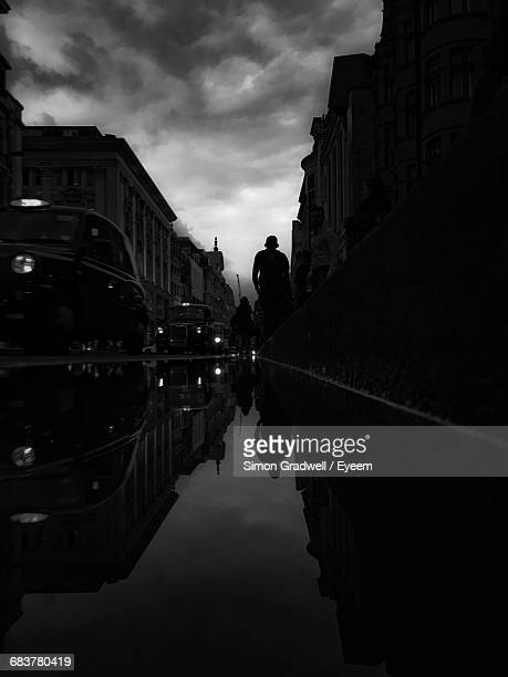 Puddle With Reflection Of People And Cars In City Against Cloudy Sky