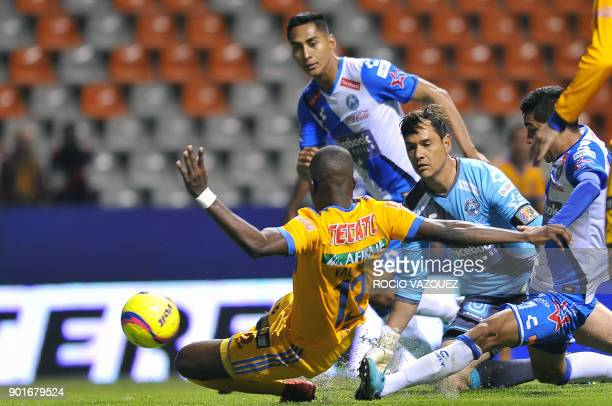Puebla's goalie Moises Munoz tries to stop a ball from Tigres' Ecuadorean player Enner Valencia during their Mexican Clausura tournament football...