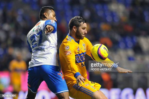Puebla's Hugo Rodriguez vies for the ball with Tigres' French player AndrePierre Gignac during their Mexican Clausura tournament football match at...