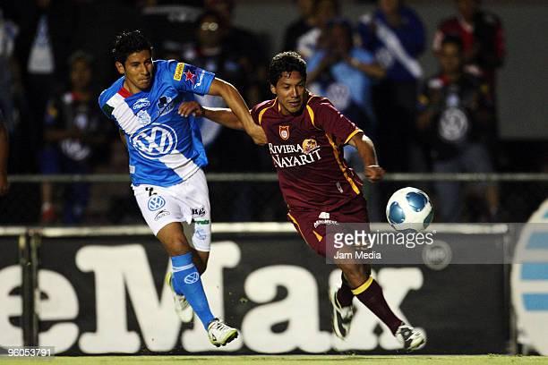 Puebla's player Orlando Javier Rincon vies the ball with Jose Ramon Partida of Estudiantes during their match at Tres de Marzo Stadium on January 22,...