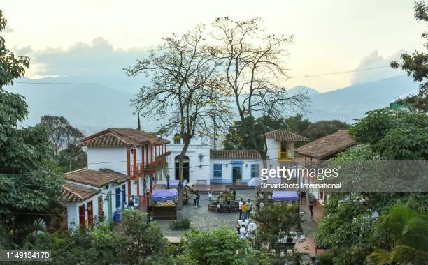 pueblito paisa main square at early dusk on cerro nutibara of medellin, antioquia, colombia - antioquia stock pictures, royalty-free photos & images