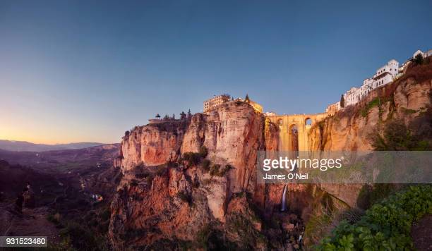 puente nuevo and the city of ronda at dusk, malaga, spain - spain stock pictures, royalty-free photos & images