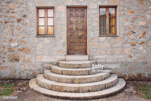 puerta principal de madera en casa con escalera de piedra - 石造りの家 ストックフォトと画像