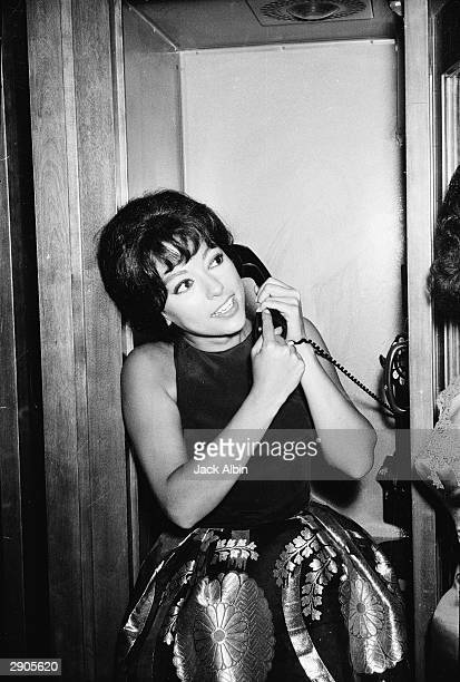 Puerto Rican actor Rita Moreno speaks on the telephone after winning the 'Actress In a Supporting Role' award for the film 'Westside Story' directed...