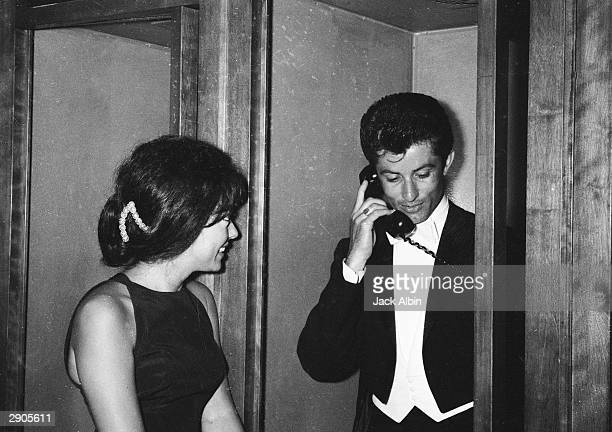 Puerto Rican actor Rita Moreno waits for George Chakiris outside a phone booth at the Academy Awards, Santa Monica, California, April 9, 1962.