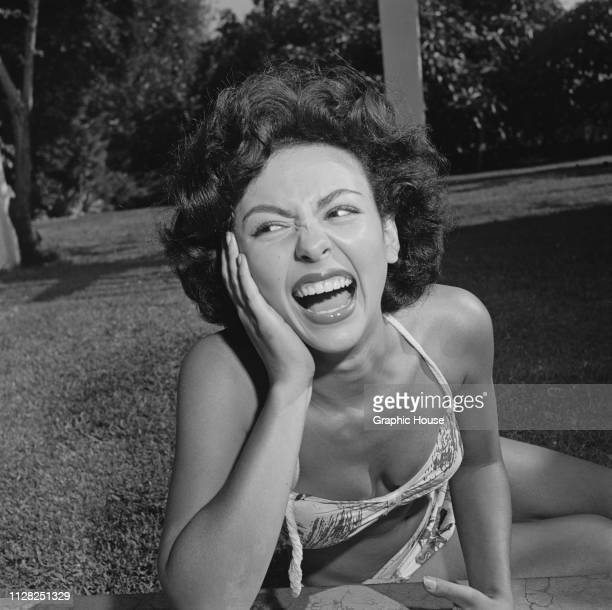 Puerto Rican actress, dancer and singer Rita Moreno laughing as she sunbathes in a bikini, US, 5th October 1951.