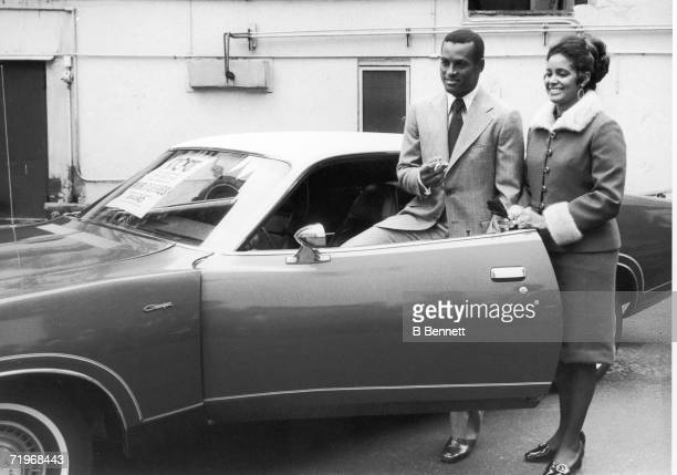 Puerto Rican baseball player Roberto Clemente of the Pittsburgh Pirates steps into a new car watched by his wife Vera New York New York October 20...