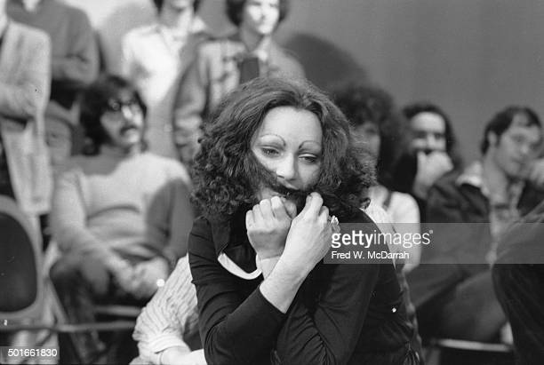 Puerto Rican drag performer and actress Holly Woodlawn holds her hair across her face on an episode of 'The David Susskind Show' devoted to Andy...