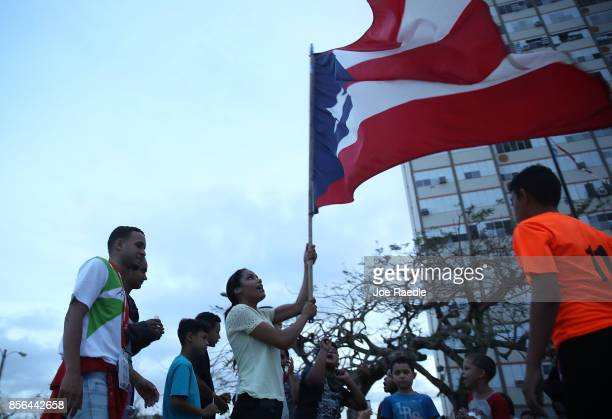 Puerto Rican flag is waved outside the Torres de Francia complex as people deal with the aftermath of Hurricane Maria on October 1 2017 in San Juan...