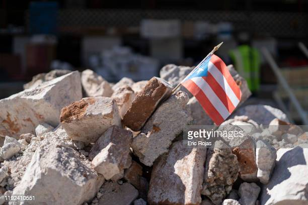 Puerto Rican flag sits in a pile of rubble after a 64 earthquake hit just south of the island on January 7 2020 in Guánica Puerto Rico This morning's...