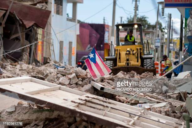 A Puerto Rican flag waves on top of a pile of rubble as debris is removed from a main road in Guanica Puerto Rico on January 8 one day after the...